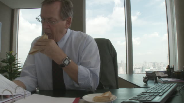 MS PAN Business man reading documents while eating sandwich in office / Bangkok, Thailand