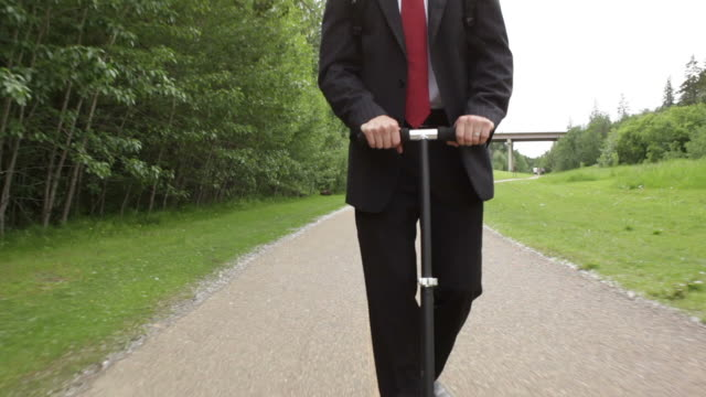business man rides a scooter to work - carbon footprint stock videos and b-roll footage