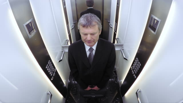 pov business man riding in the elevator - elevator point of view stock videos and b-roll footage