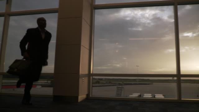 ms pan business man running through airport / jacksonville, fl, united states - jacksonville florida video stock e b–roll