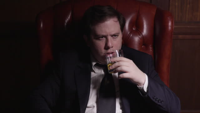 business man sips whiskey - armchair stock videos & royalty-free footage