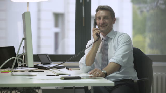 business man sitting at the desk and talking on the phone - 45 49 jahre stock-videos und b-roll-filmmaterial
