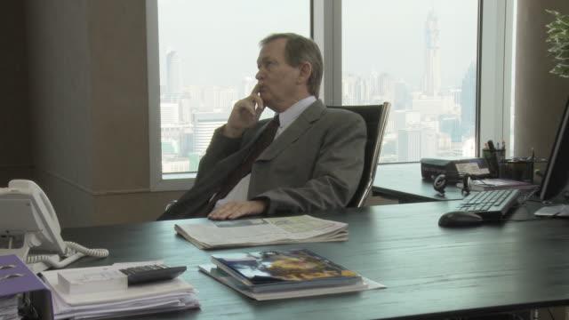 MS ZI CU Business man sitting behind desk in office / Bangkok, Thailand