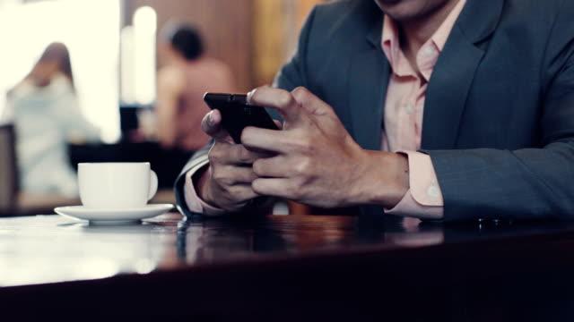 geschäftsmann, sitzen in einem café mit smartphone - abhängigkeit stock-videos und b-roll-filmmaterial