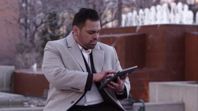 business man sitting using tablet. - ゴーティー点の映像素材/bロール