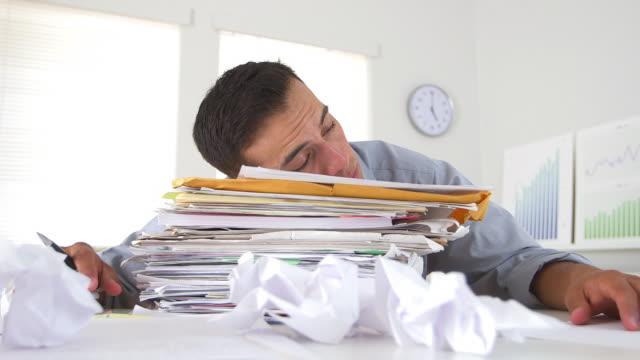 Business man sleeping on stack of paperwork