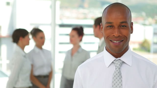 Business man smiles while looking at the camera