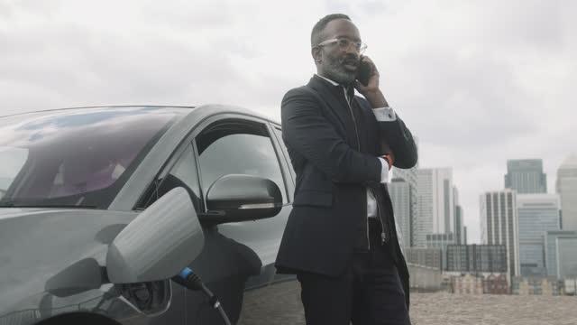 vídeos y material grabado en eventos de stock de business man speaking on smart phone leaning against charging electric car in city - coche eléctrico coche alternativo