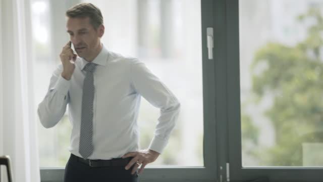 vídeos de stock, filmes e b-roll de business man standing and talking on the phone - homens maduros