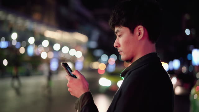 business man standing outside at night and typing on his smartphone - one man only stock videos & royalty-free footage