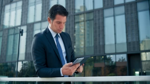 ds business man standing outside the modern business building and scrolling his tablet - dedizione video stock e b–roll