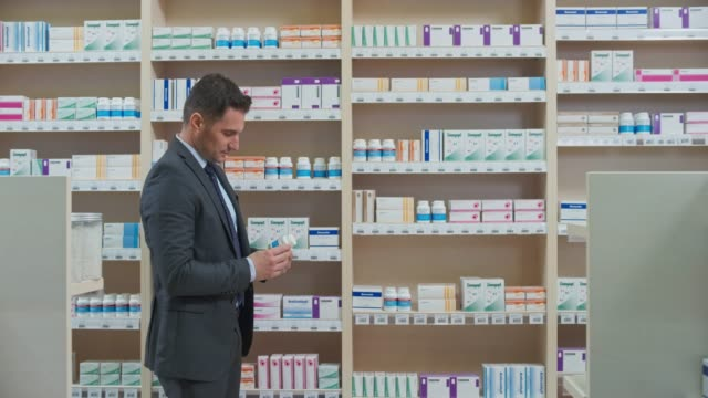 ds business man taking a container off the shelf in the pharmacy - pharmacy stock videos & royalty-free footage