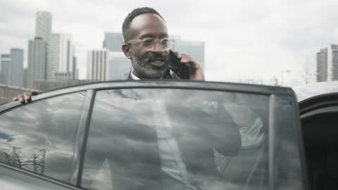 vídeos y material grabado en eventos de stock de business man talking on smart phone stepping into electric car with driver - coche eléctrico coche alternativo