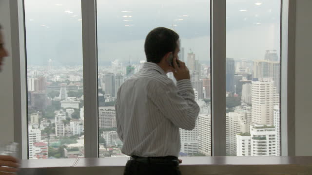 vidéos et rushes de ms business man talking on the phone by window, colleagues passing by / bangkok, thailand - homme d'affaires
