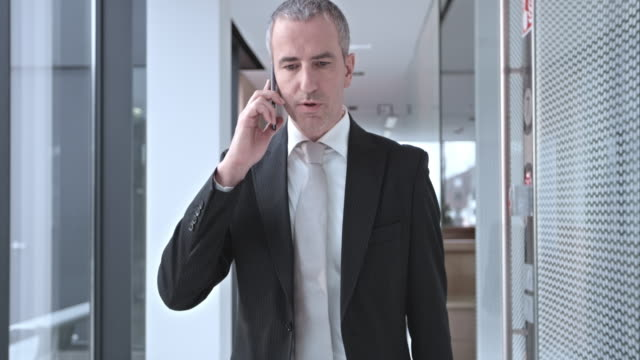 SLO MO Business man talking over phone in hallway