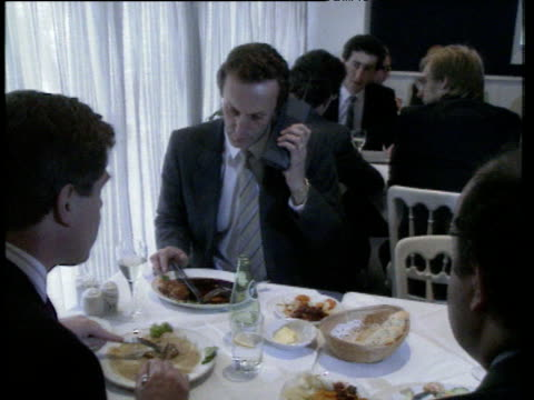 business man talks on large mobile phone and looks at watch whilst eating meal in restaurant uk; 1980s - bbc archive stock-videos und b-roll-filmmaterial