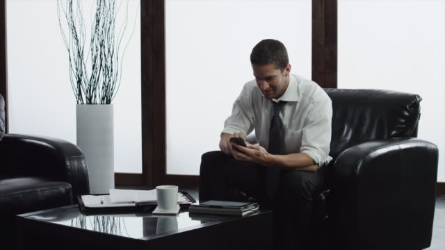 ms business man text messaging, sitting in lobby / orem, utah, usa - orem utah stock videos and b-roll footage