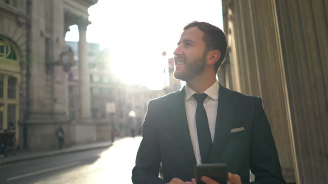 business man sms auf seinem handy außerhalb - sonnig stock-videos und b-roll-filmmaterial