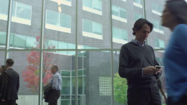 vidéos et rushes de ms ds business man texting, surrounded by people in atrium / south orange, new jersey, usa - cour intérieure