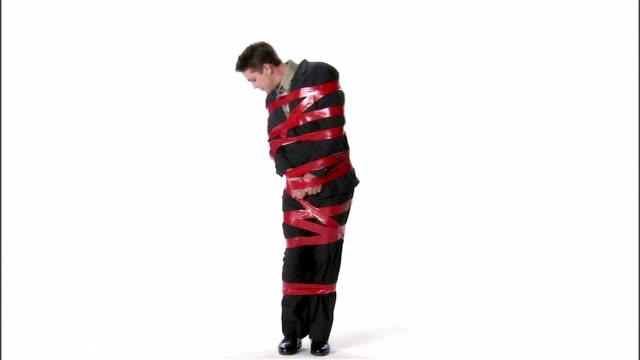 vídeos y material grabado en eventos de stock de ws, business man tied up with sticky tape, studio shot - amarrado