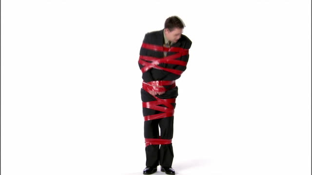 WS, business man tied up with sticky tape, studio shot