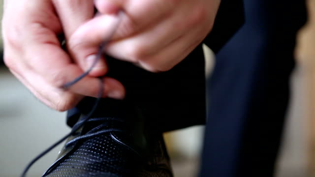 business man tying the laces on shoes. businessman dress shoes business. - leather shoe stock videos and b-roll footage