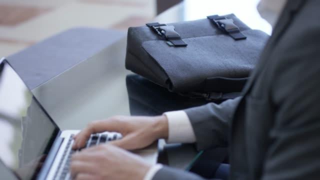 vídeos de stock, filmes e b-roll de homem de negócios, digitando em um laptop em um hall de entrada com maleta - cinza descrição de cor