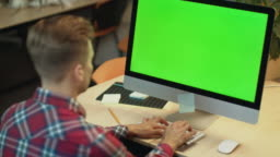 Business man typing on computer with green screen. Young man working on computer