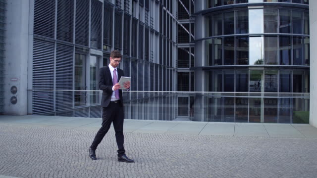Business man uses tablet while walking