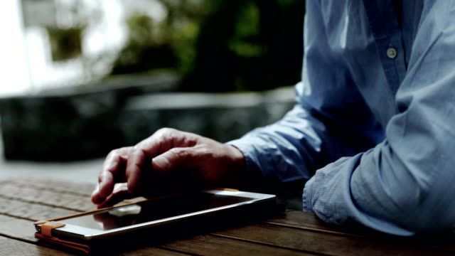Business man using a tablet PC outside
