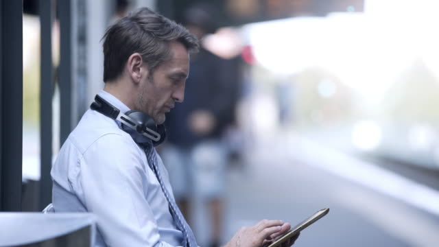 business man using his tablet at a train station - railway station platform stock videos and b-roll footage