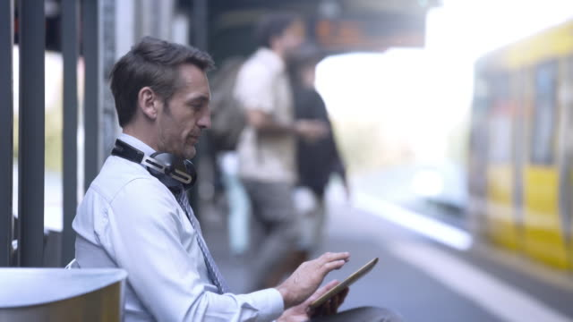 business man using his tablet at a train station - ausrüstung und geräte stock-videos und b-roll-filmmaterial