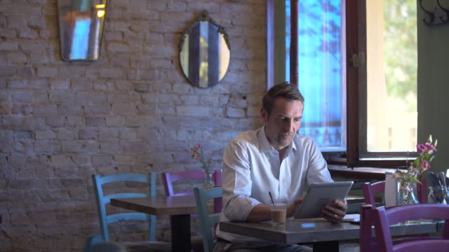 Business man using his tablet in a café