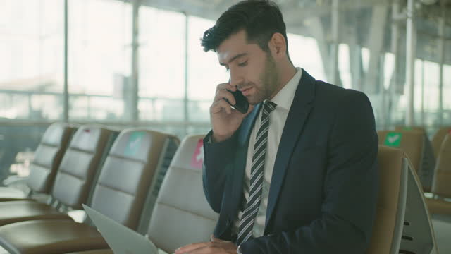 business man using laptop and mobile phone in airport. - social grace stock videos & royalty-free footage