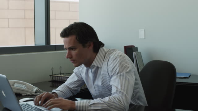 vídeos de stock, filmes e b-roll de ms pan business man using laptop in office / las vegas,nevada,usa - só um homem jovem