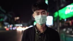 Business man using mask protection and looking at camera at night