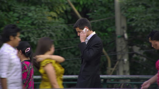 ms ts business man using mobile phone walking on footbridge over busy downtown road, bangkok, ayuthaya, thailand - see other clips from this shoot 1448 stock videos and b-roll footage