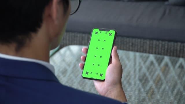 vídeos de stock, filmes e b-roll de homem de negócio que usa a tela verde do telefone - portable information device