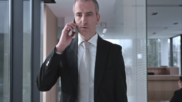 slo mo ds business man using phone in hallway - mature adult stock videos & royalty-free footage