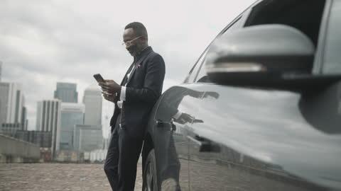 vídeos y material grabado en eventos de stock de business man using smart phone leaning against electric car in city - coche eléctrico coche alternativo