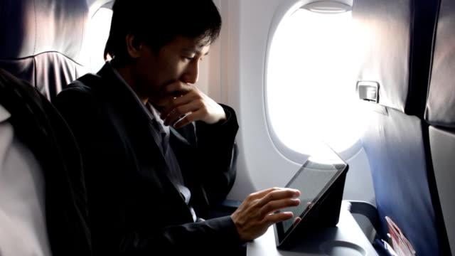 飛行機でタブレットを使用してビジネスの男性 - 錠剤点の映像素材/bロール