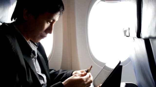 business man using tablet on the plane while eating