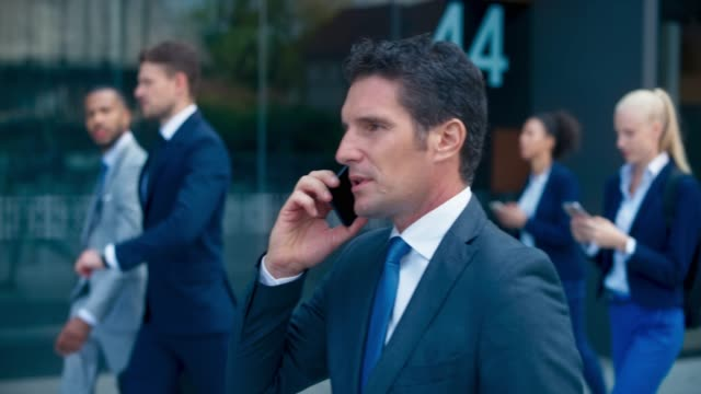 slo mo ts business man walking along the business building and talking on the phone - business person stock videos & royalty-free footage
