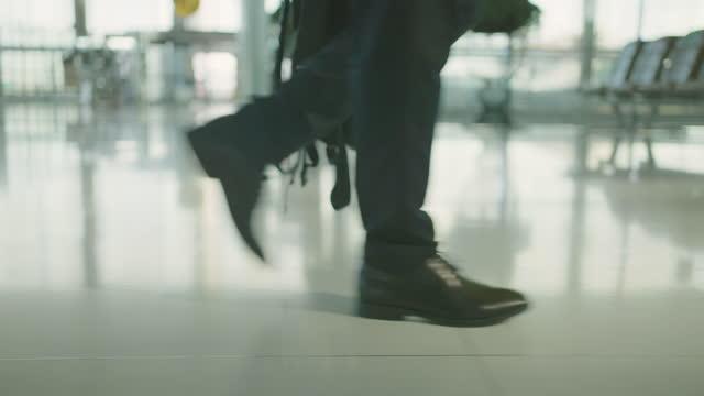 vídeos de stock, filmes e b-roll de homem de negócios andando e correndo no aeroporto. - mochila bolsa