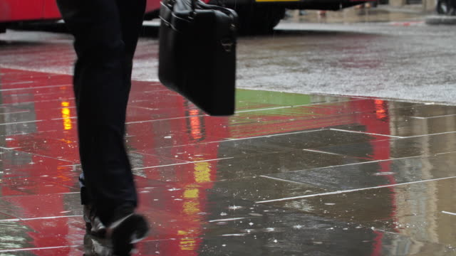 business man walking in the rain. - weather stock videos & royalty-free footage