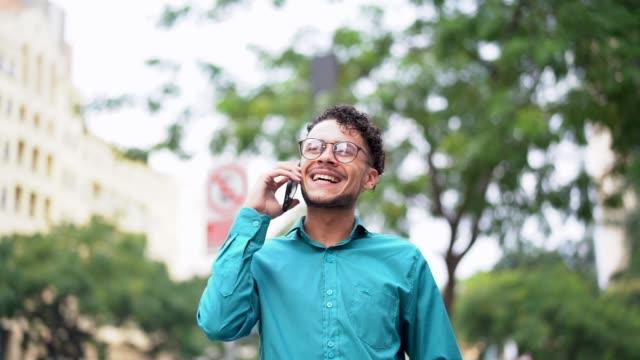 vídeos y material grabado en eventos de stock de hombre de negocios caminar utilizando móviles sobre la marcha - hombres jóvenes