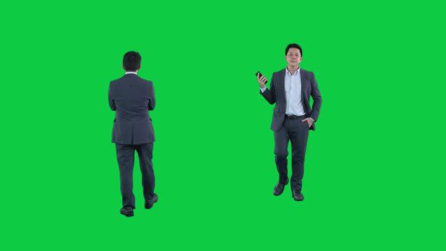 business man walking with smart phone on green screen ,4k footage with alpha chanel.codeck-png+alpha. - plain background stock videos & royalty-free footage