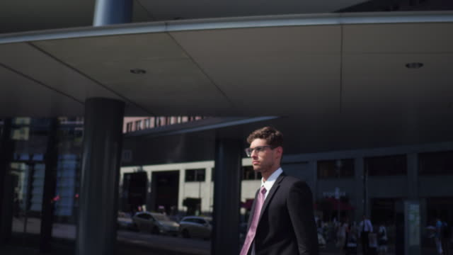 Business man walks between office buildings and checks phone
