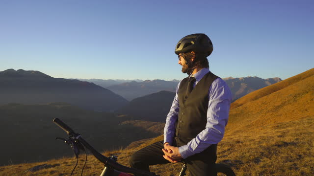 business man wearing suit sitting on top of bicycle on mountain top adjusting tie, looks out to enjoy sunset - offbeat stock videos & royalty-free footage