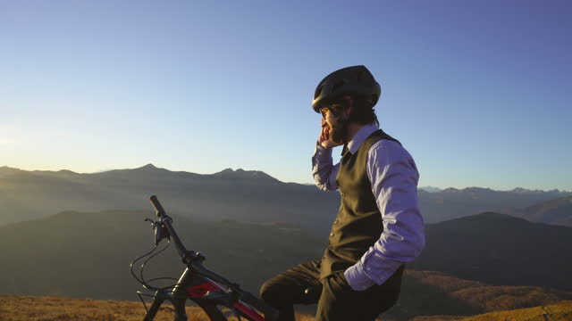 business man wearing suit sitting on top of bicycle on mountain top answering phone call - cycling helmet stock videos & royalty-free footage